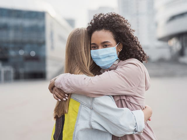 Two people embrace each other during the pandemic