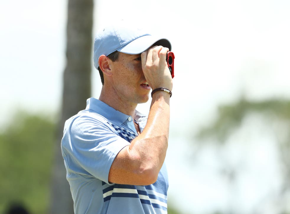 Rory McIlroy uses a rangefinder during a practice round