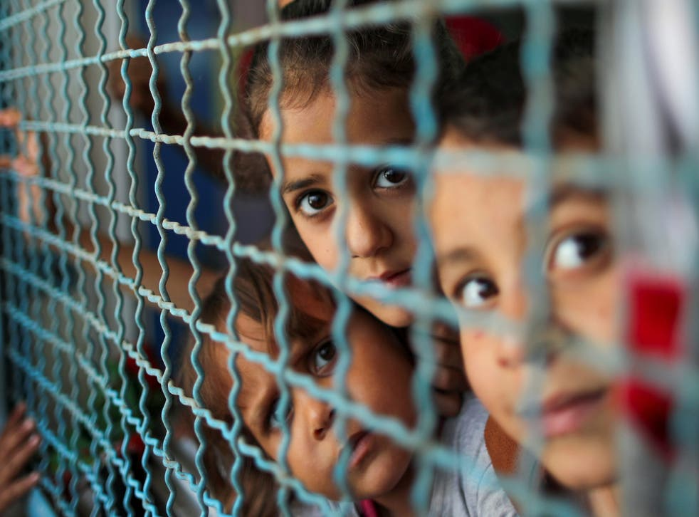 Palestinian children, who fled their homes due to Israeli air and artillery strikes, look through a window fence at a United Nations-run school where they take refuge, in Gaza City