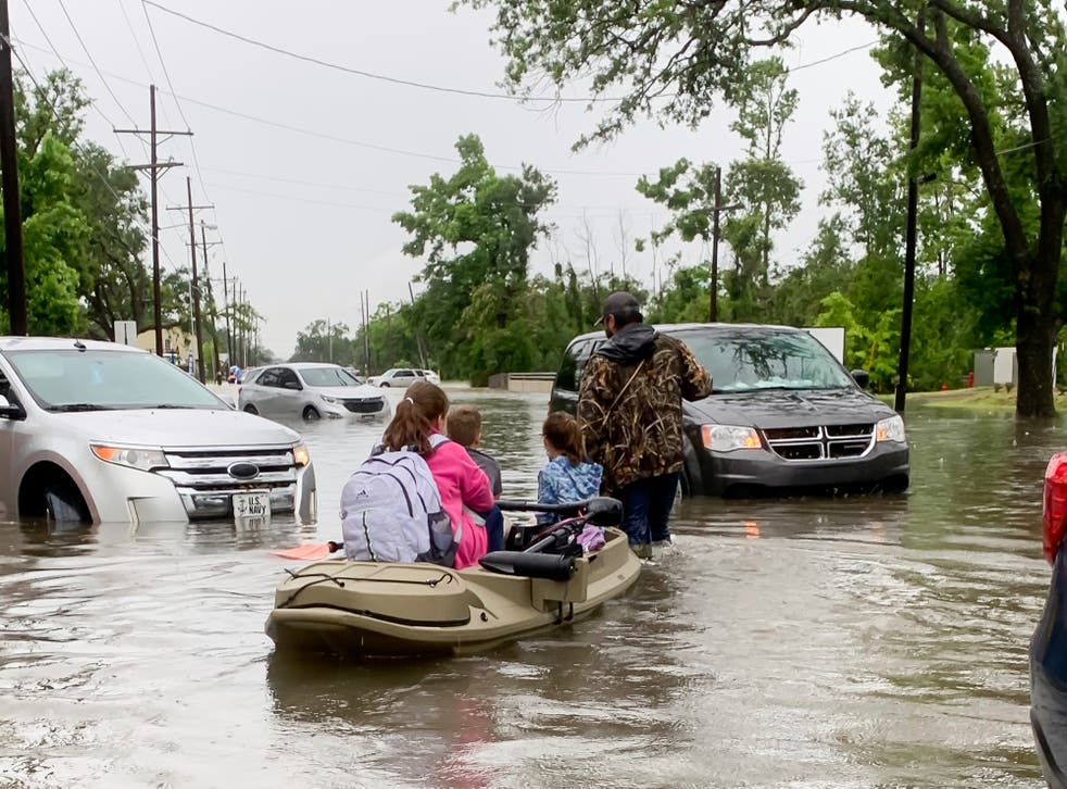 <p>Parents use boats to pick up students from schools after nearly a foot of rain fell in Lake Charles, Louisiana on 17 May.</p>