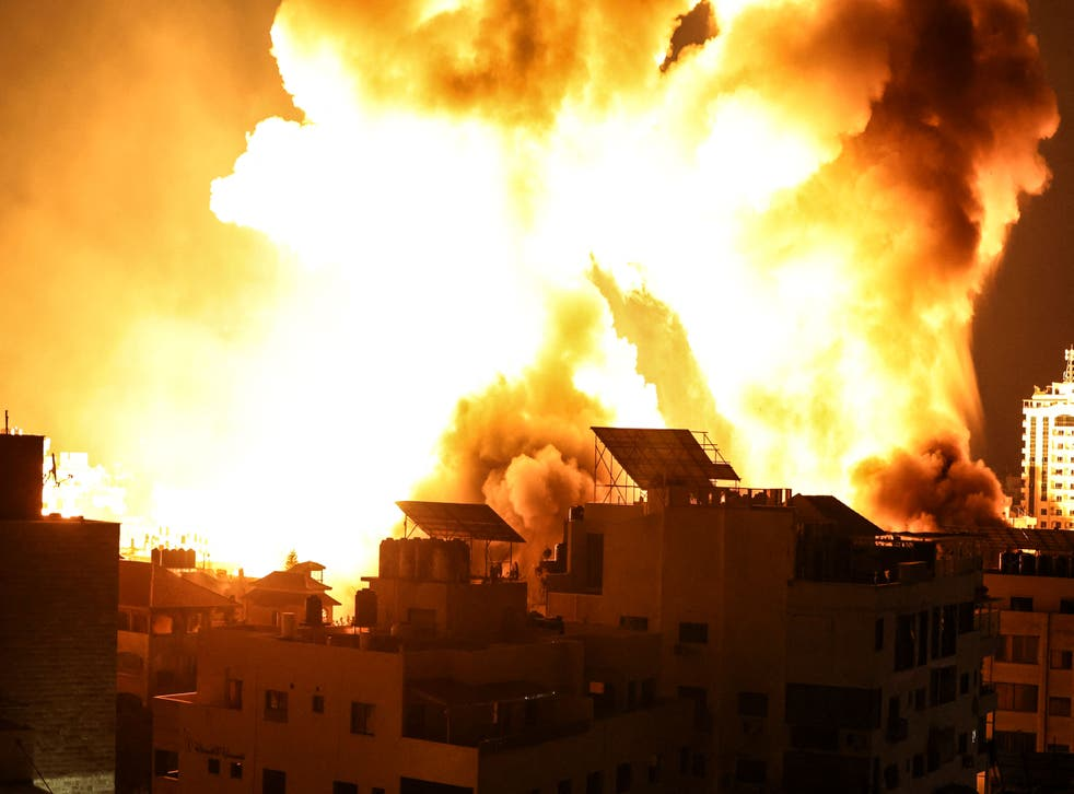 A ball of fire explodes above buildings in Gaza City as Israeli forces shell the Palestinian enclave, early on May 18, 2021