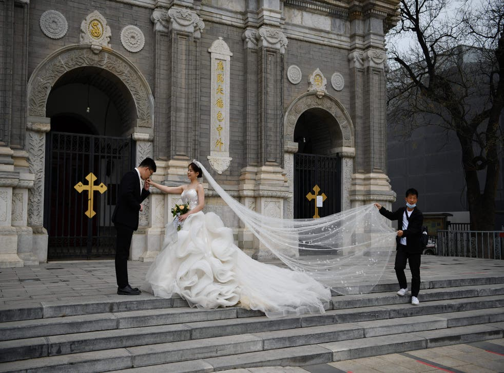 <p>A couple poses for wedding photos outside St Joseph's Church, also known as Wangfujing Catholic Church, in Beijing </p>