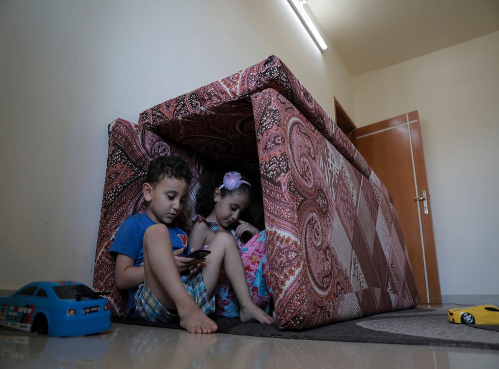 <p>Shelter and play: Jamal Mghames and his sister, Joury, with their fort of cushions at home in Gaza City during the recent bombing </p>