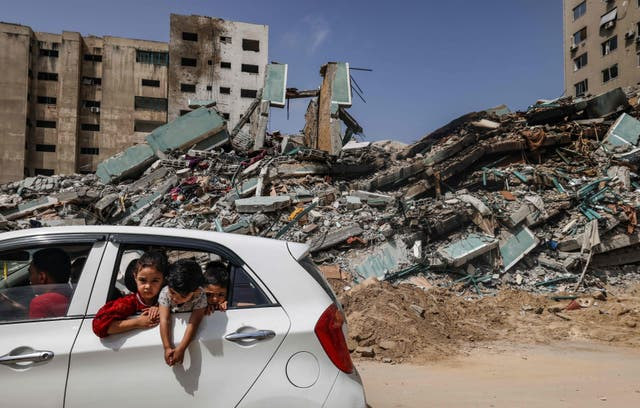 Palestinians drive past the Al-Jalaa Tower in Gaza City, a building that hosted the offices of the Associated Press news agency as well as the Al-jazeera English television channel, levelled by an Israeli air strike.