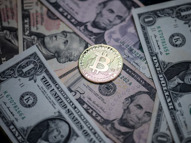 A physical imitation of the Bitcoin crypto currency displayed on US dollars bank notes