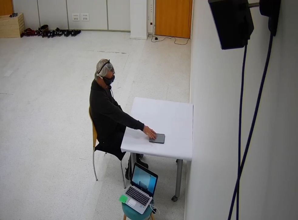 The patient doing a test of perceiving, locating, touching, and counting various objects placed on a white table while wearing light-stimulating goggles