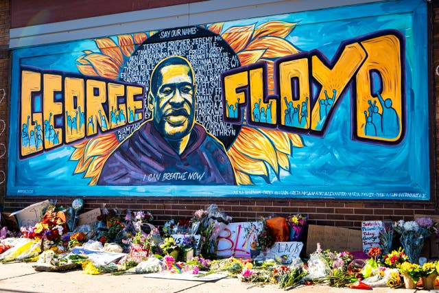 George Floyd mural with flowers laid in front