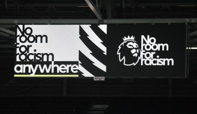 A big screen displaying a No Room For Racism video