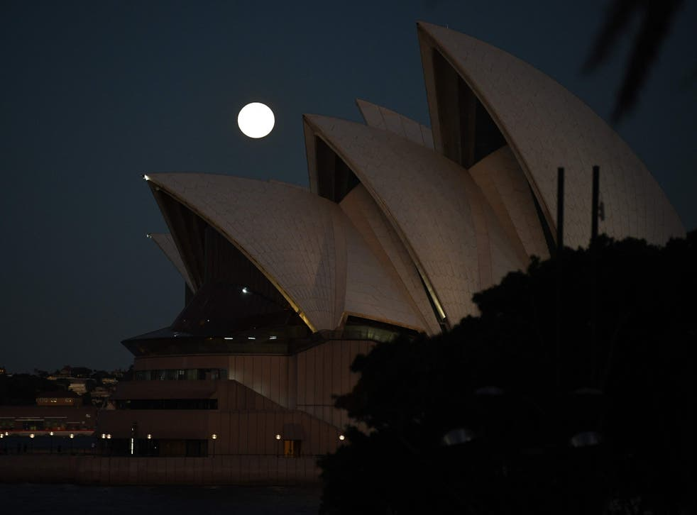 <p>The moon rises over Sydney Opera House in Australia on Wednesday 26 May 2021</p>