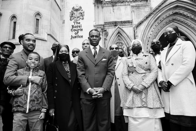 <p>The claimants stand outside the High Court following their victory</p>