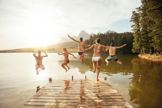 Friends leaping into a lake