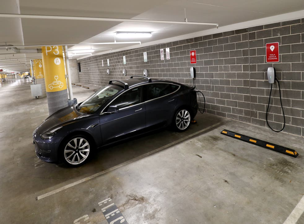 <p>A Tesla Model Y charges at a EV charge station in Lane Cove, Australia</p>