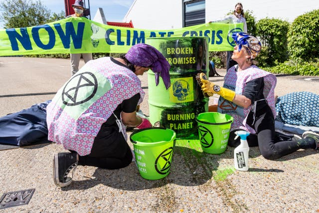 <p>Protesters remove paint from oil drums, symbolically washing away the 'soothing promises peddled by the UK Government and fossil fuel industry'</p>