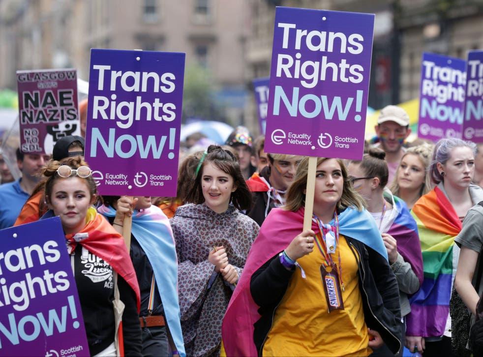 <p>Personas que portan pancartas de derechos trans participan en el desfile del Orgullo en Glasgow</p>