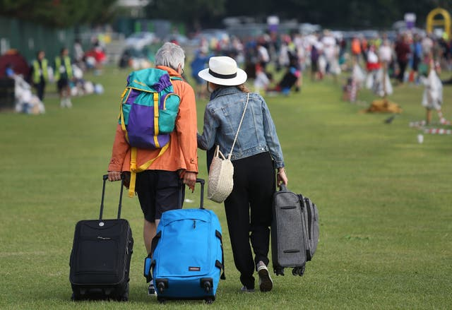 A man and woman pull suitcases across grass