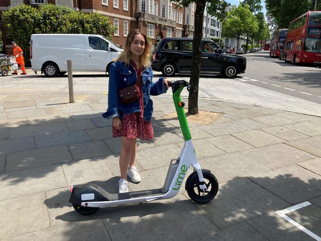 <p>Beata Onikul, 20, hires a rental e-scooter in South Kensington, London, on the first day of a 12-month government-backed trial</p>