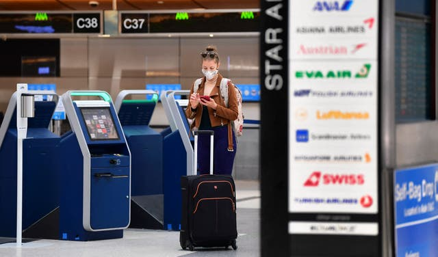 <p>A woman checks her cellphone by self check-in kiosks on the departures level of Los Angeles International Airport (LAX) on May 27, 2021 in Los Angeles.</p>