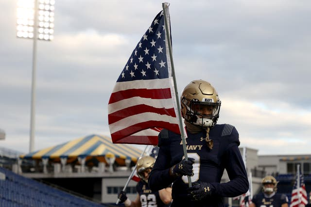 <p>ANNAPOLIS, MARYLAND - DECEMBER 05: Cameron Kinley #3 of the Navy Midshipmen carries an American flag as the team takes the field against the Tulsa Golden Hurricane at Navy-Marine Corps Memorial Stadium on December 05, 2020 in Annapolis, Maryland. </p>