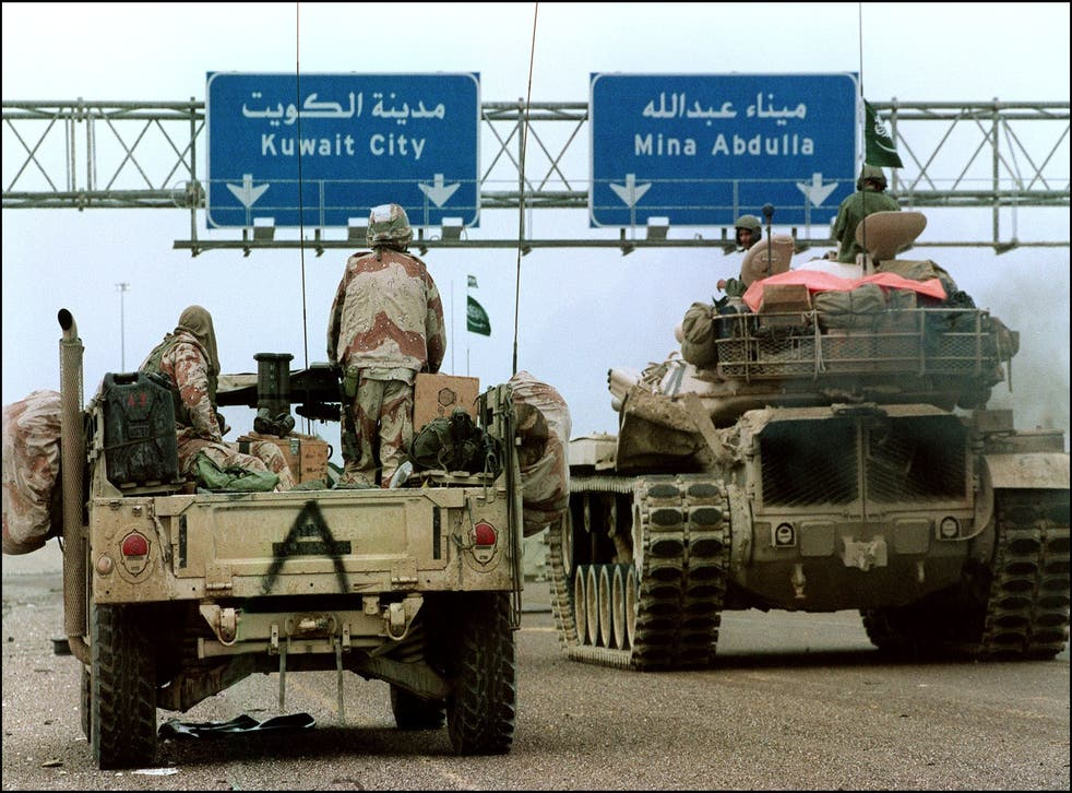<p>A US Humvee and a Saudi tank pass under a sign directing them to Kuwait City in February 1991 during the Desert Storm offensive</p>