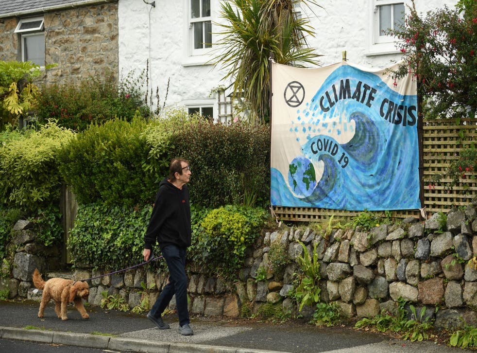 <p>A man walks past a banner displayed on a garden wall in St Ives, Cornwall, ahead of the three-day G7 summit being held from 11-13 June</p>