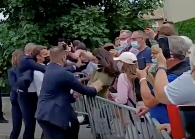 <p>French President Emmanuel Macron is protected by a security member after getting slapped</p>