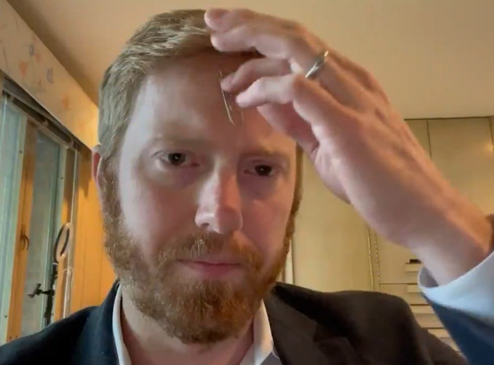 <p>Republican congressman, Peter Meijer holds the paper clip to his head to debunk  vaccine conspiracy theory</p>
