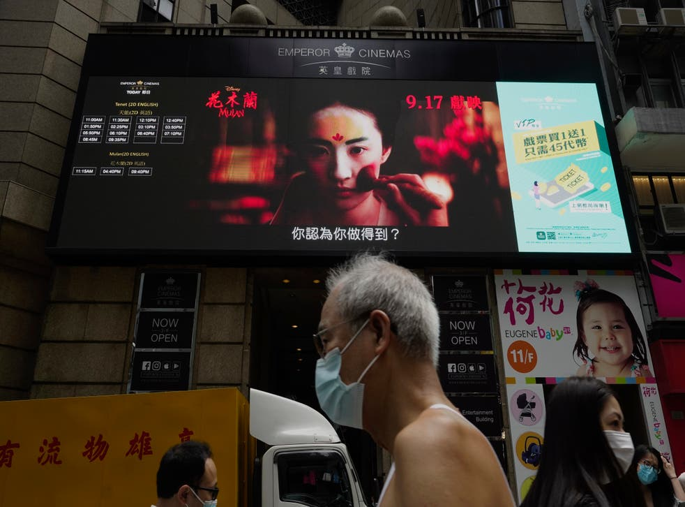 """<p> Imagen de archivo: en esta imagen del jueves 17 de septiembre de 2020, la gente pasa junto a una enorme pantalla de televisión que muestra la programación de películas """"a lo largo de una calle del centro de Hong Kong </p>"""