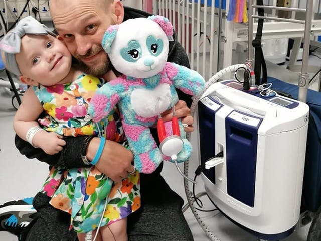 <p>Baby Grace with father Darren and her new portable heart pump</p>