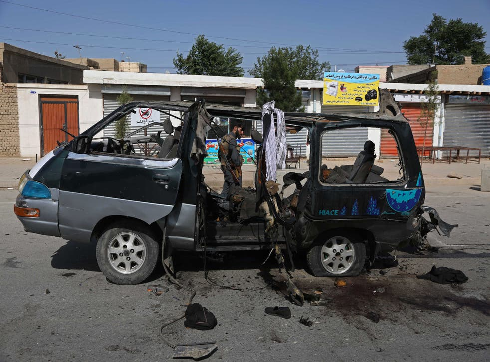 <p>A security personnel stands next to a damaged vehicle at the site of an explosion in Kabul on June 3, 2021. At least seven people have been killed in two new attacks on minivans.</p>
