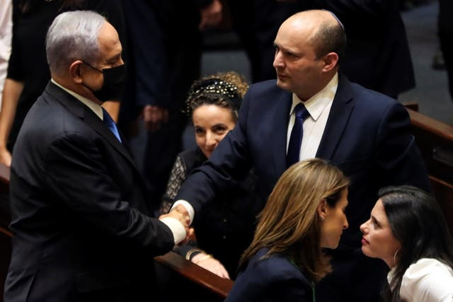 <p>El jefe de la oposición, Benjamin Netanyahu, y el primer ministro de Israel, Naftali Bennett, se dan la mano tras la votación sobre la nueva coalición en la Knesset, el parlamento de Israel.</p>