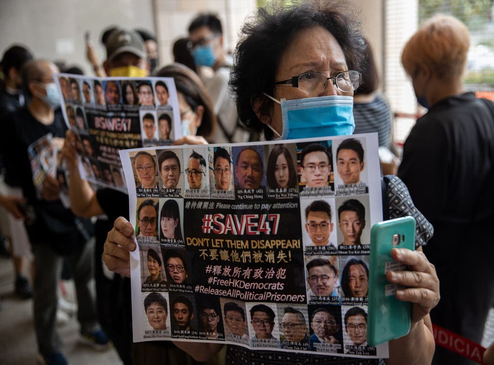 <p>A supporter holds a poster of pro-democracy figures on trial under the new national security law</p>
