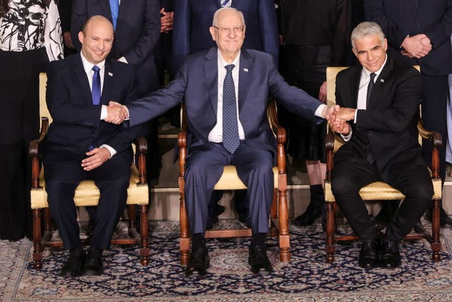 <p>Israel's President Reuven Rivlin between Prime Minister Naftali Bennett and Foreign Minister Yair Lapid as they pose for a group photo with ministers of the new Israeli government</p>