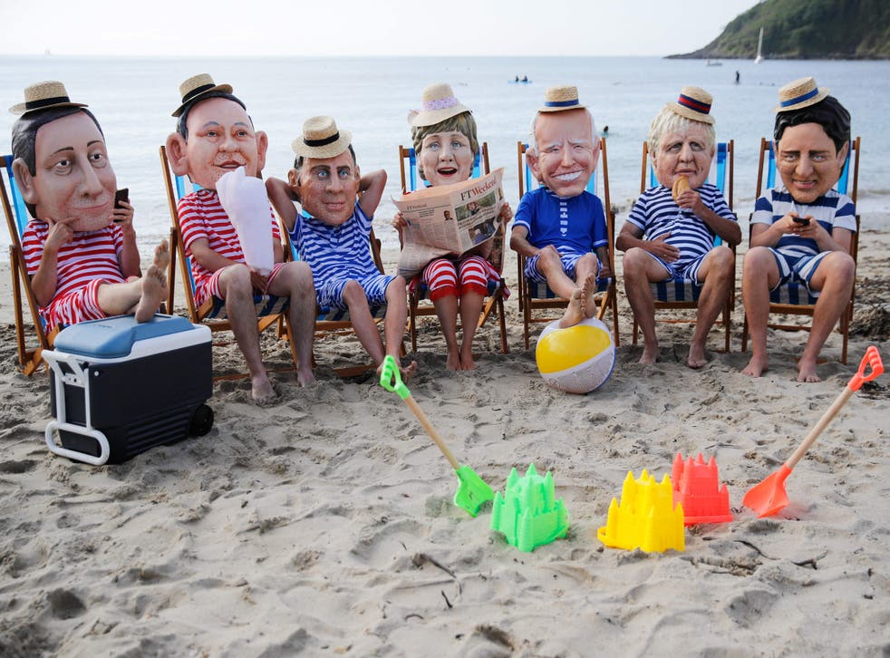 <p>Oxfam activists wearing papier mache heads representing G7 leaders perform during a protest near Falmouth</p>