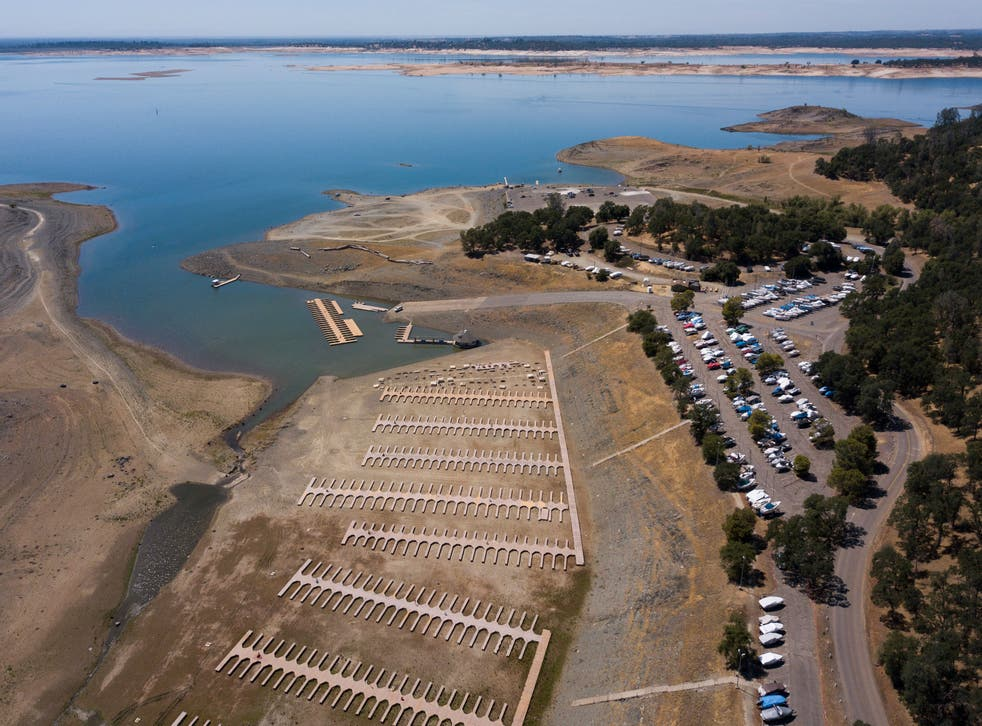 <p>An aerial image shows boats stored in a parking lot after the Folsom Lake Marina closed due to dry lake bed conditions during the California drought emergency on May 27, 2021 in El Dorado Hills, California. A plane wreckage found at the bottom of the lake could solve a decades-old mystery. </p>