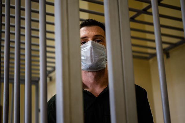 <p>US ex-marine Trevor Reed, then charged with attacking police, stands inside a defendants' cage during his verdict hearing at Moscow's Golovinsky district court on 30 July, 2020. </p>