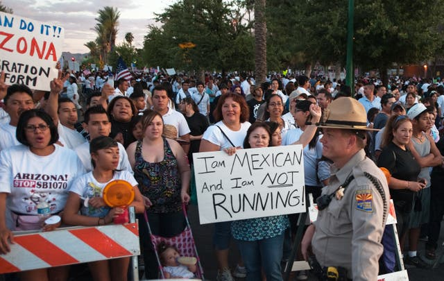 <p>Protesters gather around the Arizona State Capitol against the State Senate bill 1070, which eventually passed and allowed law enforcement to inquire about people's immigration status during arrests. (PAUL J. RICHARDS/AFP via Getty Images)</p>