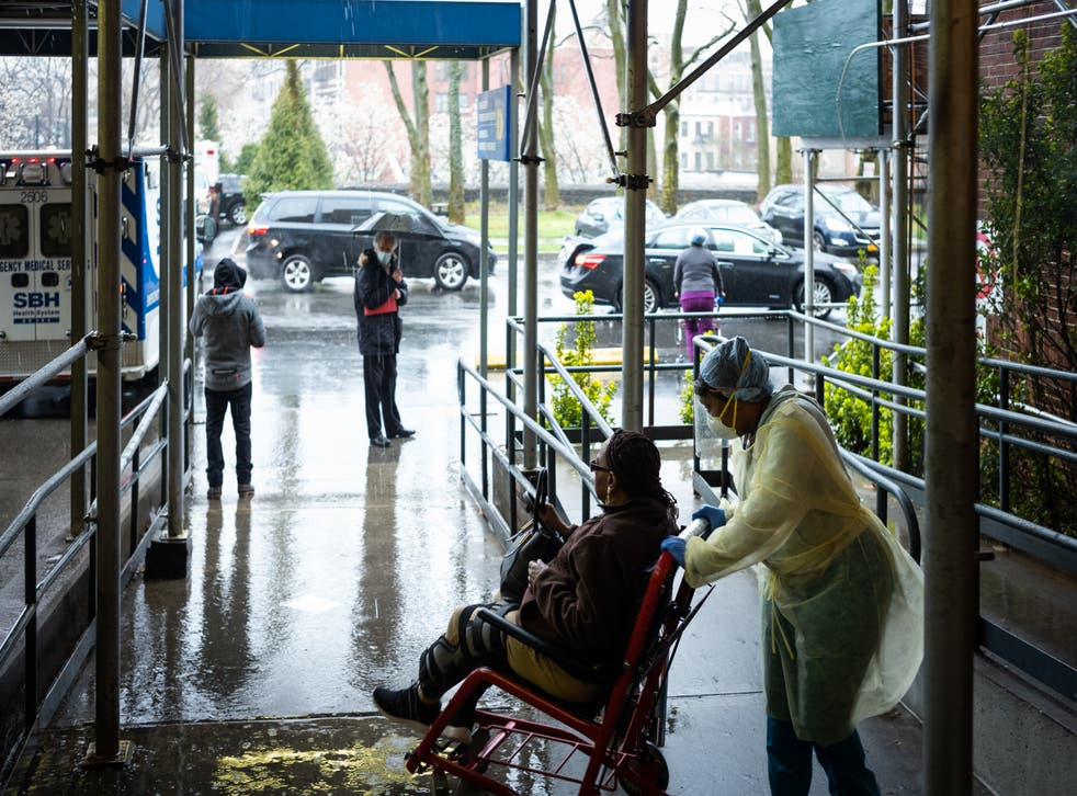 <p>A staff member pushes a patient in a wheelchair at St Barnabas Hospital on 23 March, 2020 in the Bronx borough of New York City. </p>
