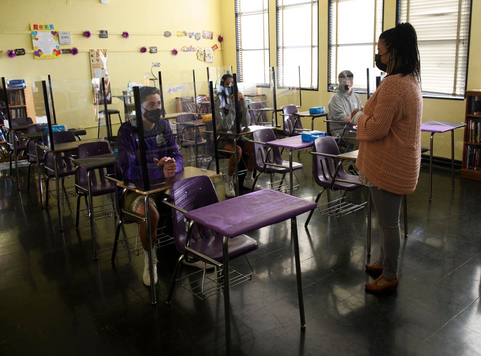 <p>A teacher speaks with students as they return to in-person learning at St. Anthony Catholic High School during the Covid-19 pandemic on March 24, 2021 in Long Beach, California. A record-breaking level of US workers are leaving their jobs for new roles.</p>