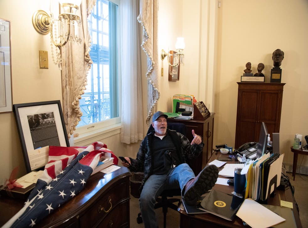 <p>Richard Barnett, a supporter of US President Donald Trump, sits inside the office of US Speaker of the House Nancy Pelosi as he protest inside the US Capitol in Washington, DC, 6 January, 2021. </p>