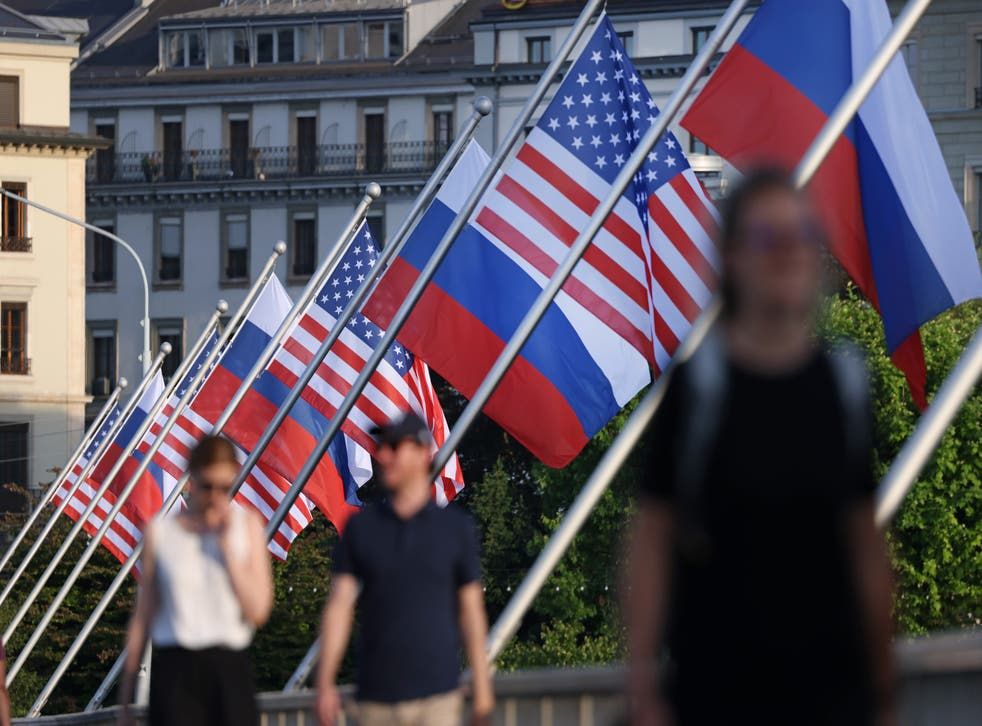 <p>People walk under Russian and American flags on a bridge in Geneva prior to the meeting between Joe Biden and Russian Vladimir Putin</p>