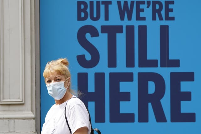 A woman wearing a mask walks past an advert outside Curry's PC World