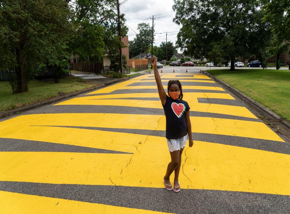 <p>Kainaan Jones, 9, poses on 'Black Towns Matter' painted on a street on 19 June, 2020 in Houston, Texas.</p>