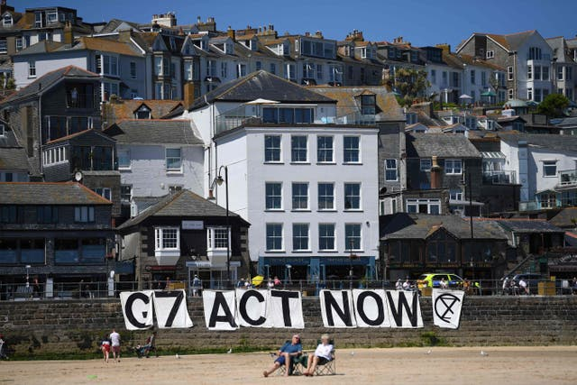 <p>Extinction Rebellion environmental activists attach a banner calling on G7 leaders to act on climate change on the beach in St Ives, Cornwall during the G7 summit on June 13, 202</p>