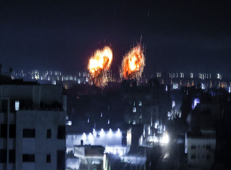 <p>Explosions lit up the night sky about building in Gaza city as Israeli forces shelled the Palestinian enclave, in response to incendiary balloons.</p>