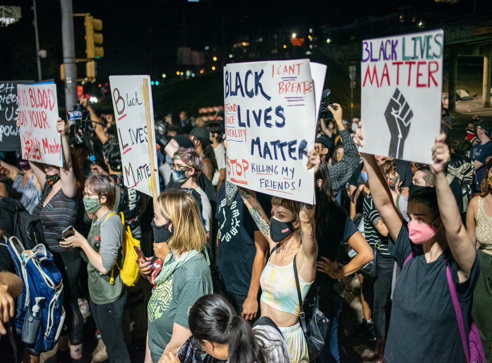 <p>Demonstrators in Austin, Texas, hold up Black Lives Matter signs on 26 July, 2020.</p>