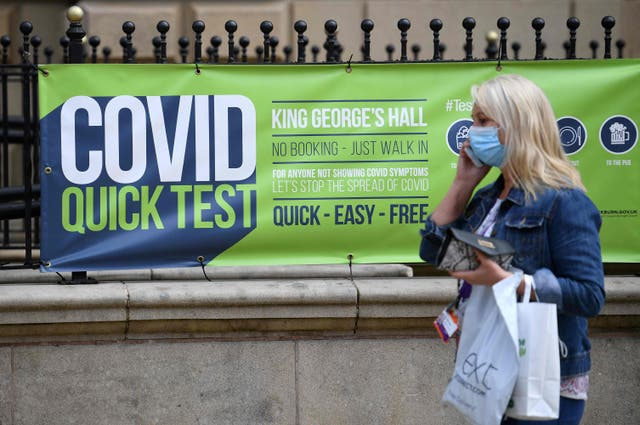 <p>A person wearing a face covering walks past a sign for a walk-in Covid-19 testing centre in Blackburn </p>