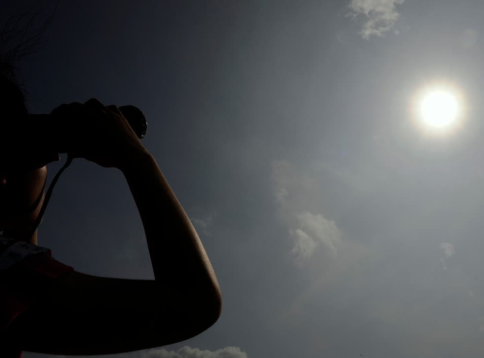 <p>File image: A woman in Hong Kong looks through binoculars as planet Venus orbits between the Sun and the Earth during the transit of Venus on 6 June, 2012.  Earth's energy imbalance is the difference between the amount of energy it receives and from sun and radiates back </p>