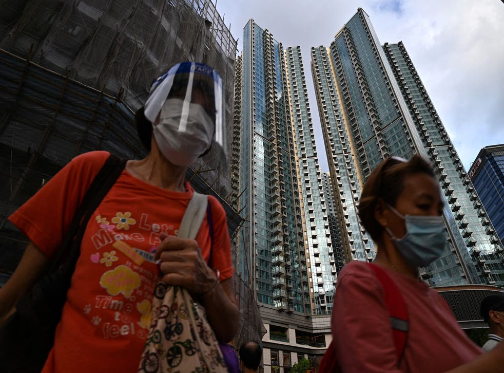 <p>Pedestrians walk past the Grand Central residential building complex in Hong Kong on 28 May 2021, where a $1.4m one-bedroom apartment has been offered for a lucky draw's grand prize for which all Hong Kong residents aged 18 and above who have received both doses of the Covid-19 vaccines will be eligible to register</p>