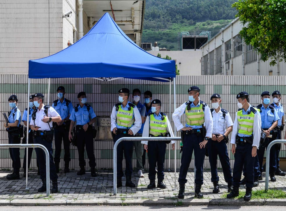 <p>Police stand guard near the offices of the local Apple Daily newspaper in Hong Kong on Thursday after police arrested five executives</p>