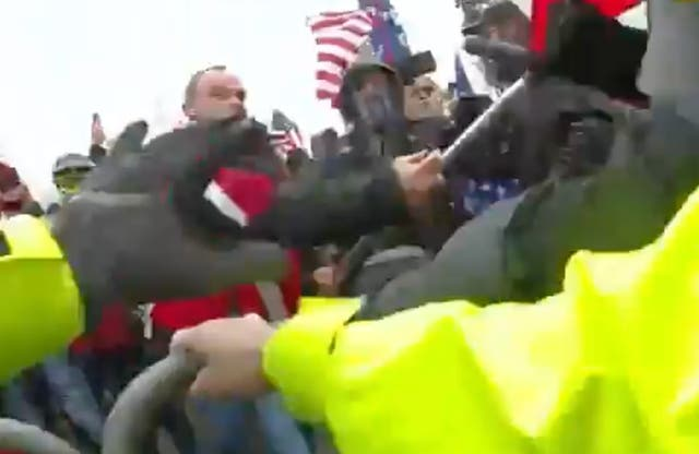 <p>Thomas Webster, wearing a red jacket, accused of attacking police with flagpole during US Capitol attack on 6 January 2021.</p>